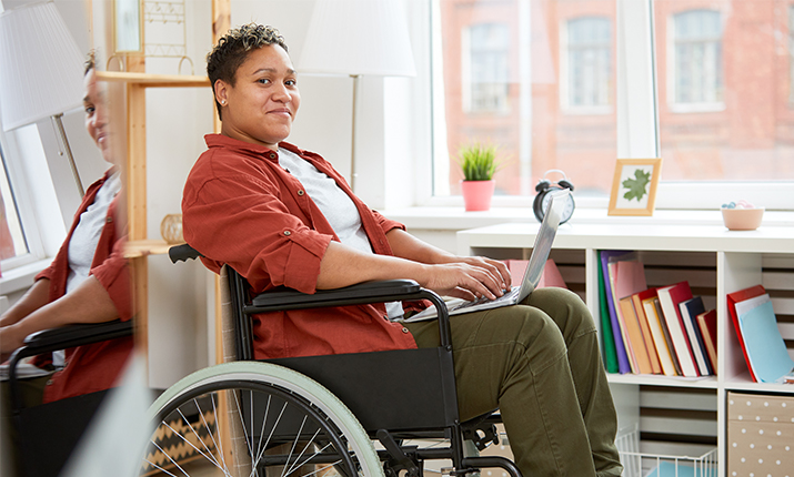 person in wheelchair with laptop rested on their lap