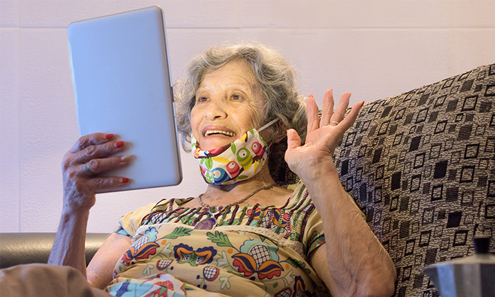 elderly woman holding and looking into a smart tablet with one hand in the air