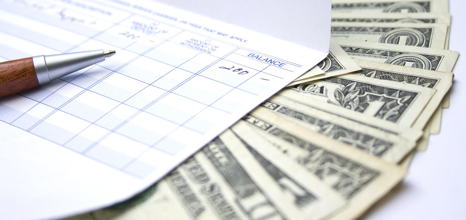 Close up image of US dollars and an account balance sheet