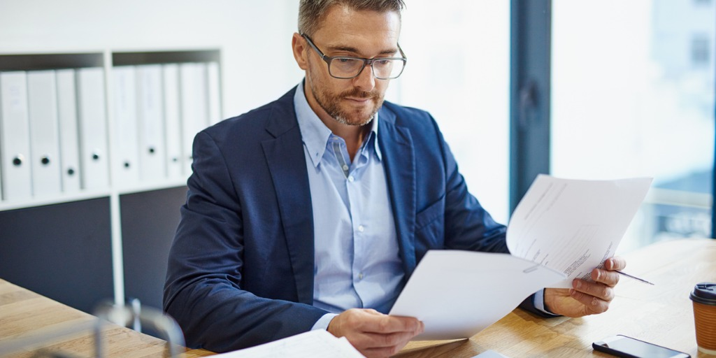 Businessman sitting at desk looking at work documents