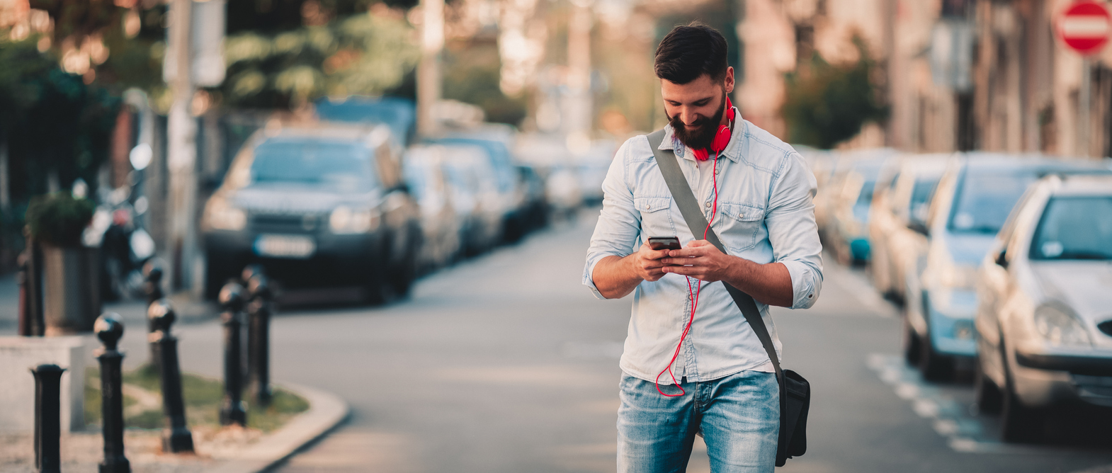 man standing in street looking down at his phone