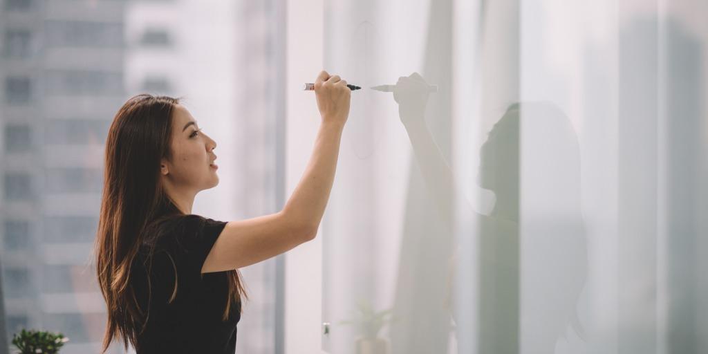 woman writing on blank whiteboard