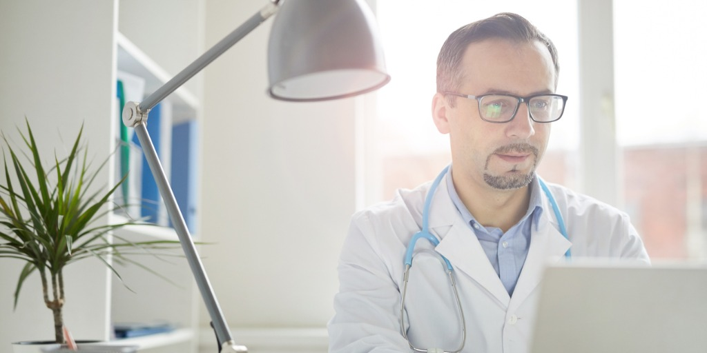 Mature male doctor in eyeglasses concentrating on his work he working on laptop at the table at office