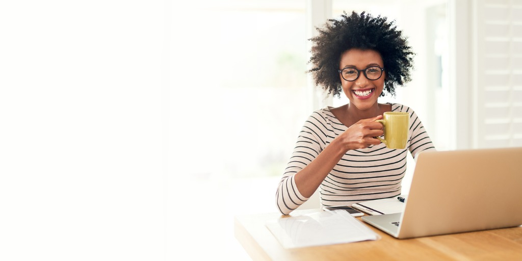 a young woman drinking coffee while working on her laptop at home