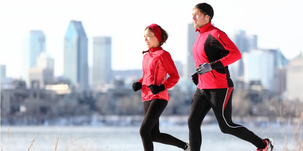 Runners running in winter snow with city background