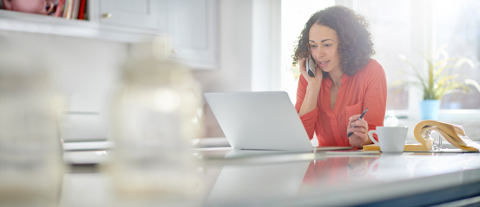woman doing work on laptop while on the phone