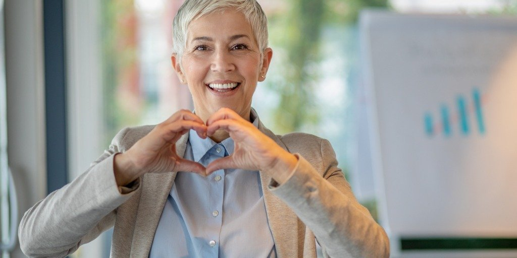 woman in a business office making the heart symbol with her hands