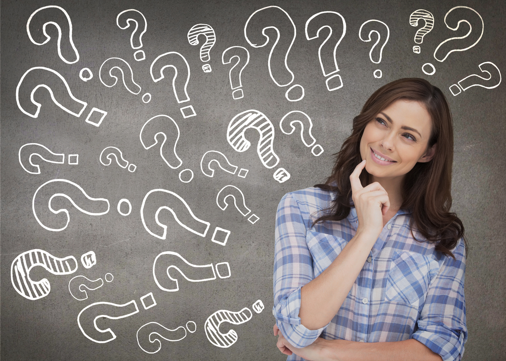 woman thinking in front of black chalkboard with several white question marks