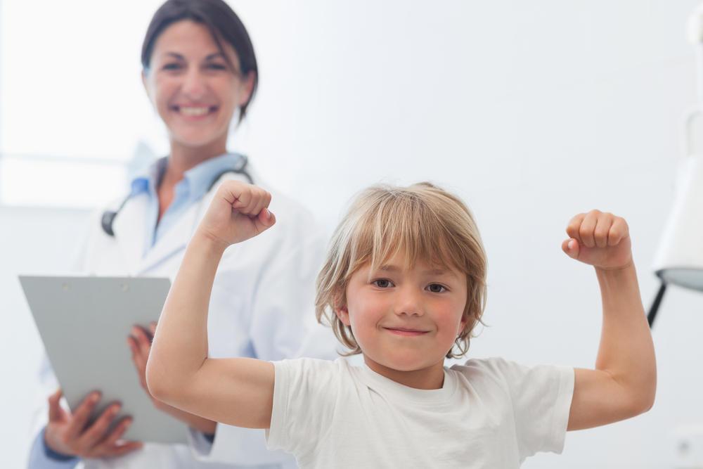 child flex his muscles in front of smiling female doctor