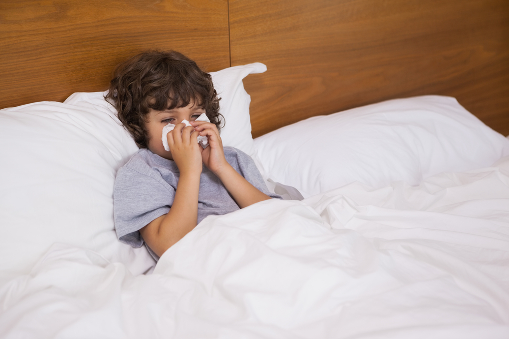 child sick in bed holding tissue to their face