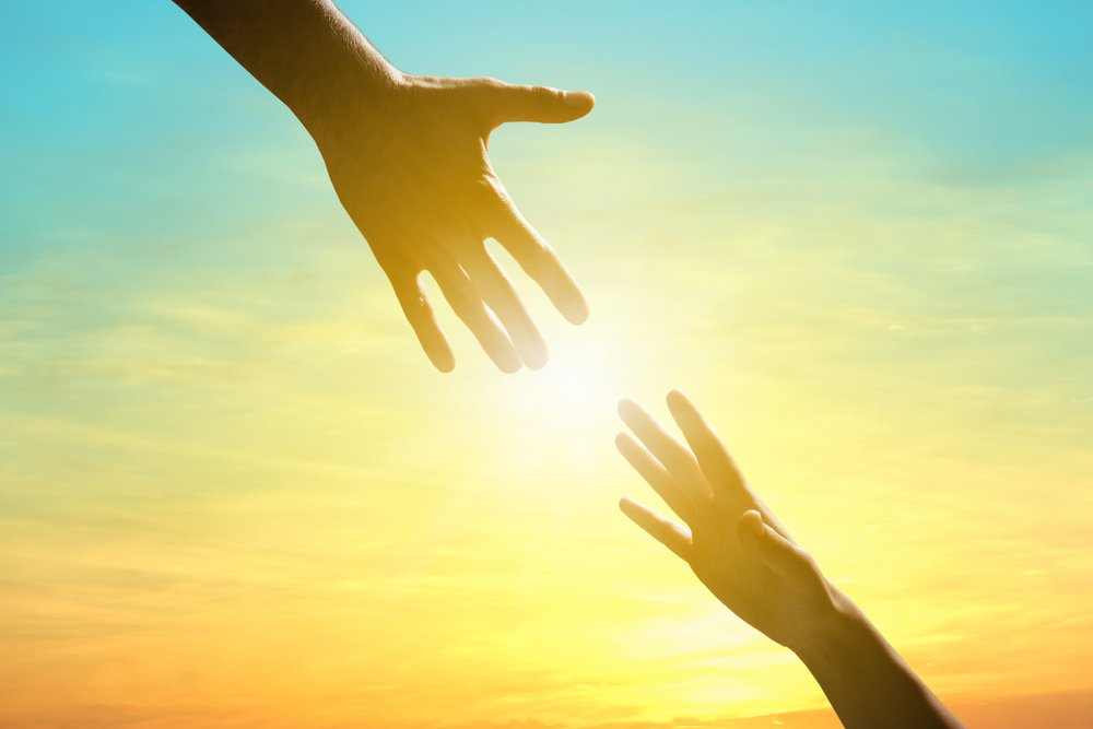 two hands reaching towards each other in front of sunlight
