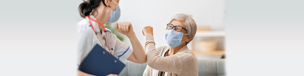 masked patient and masked doctor bumping elbows