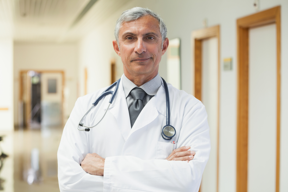 male doctor smiling with hands folded