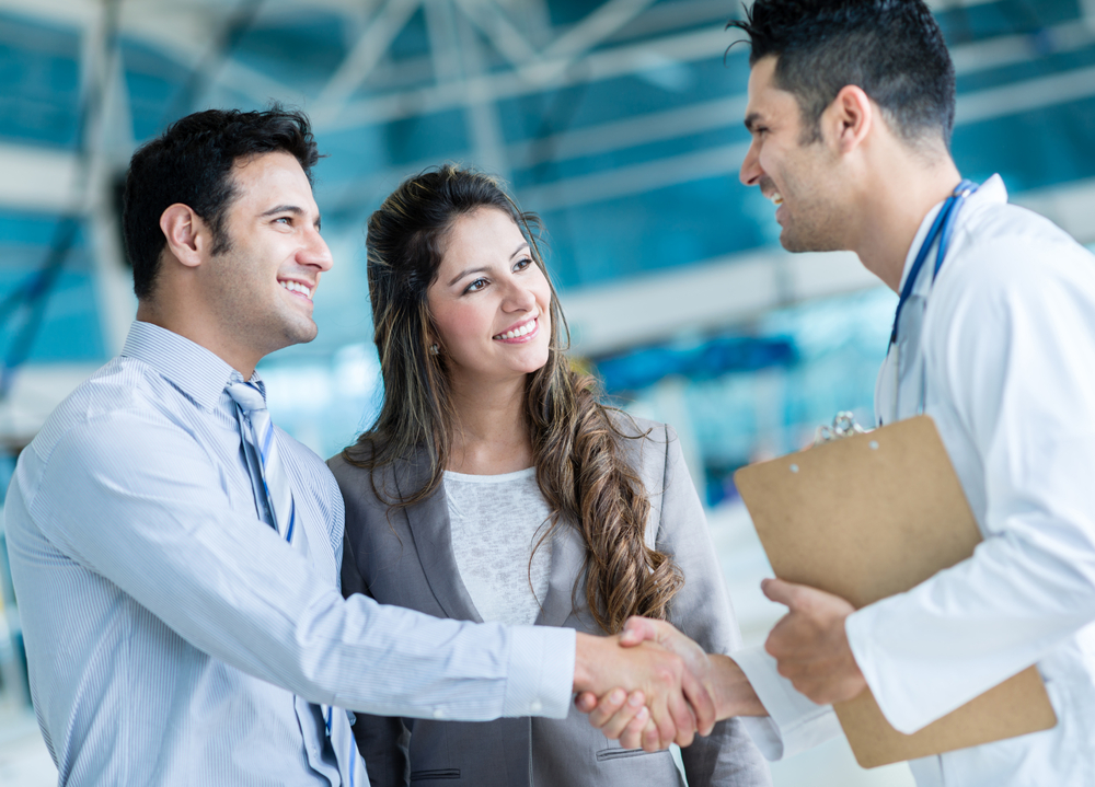 doctor shaking hands with couple as he holds a clipboard