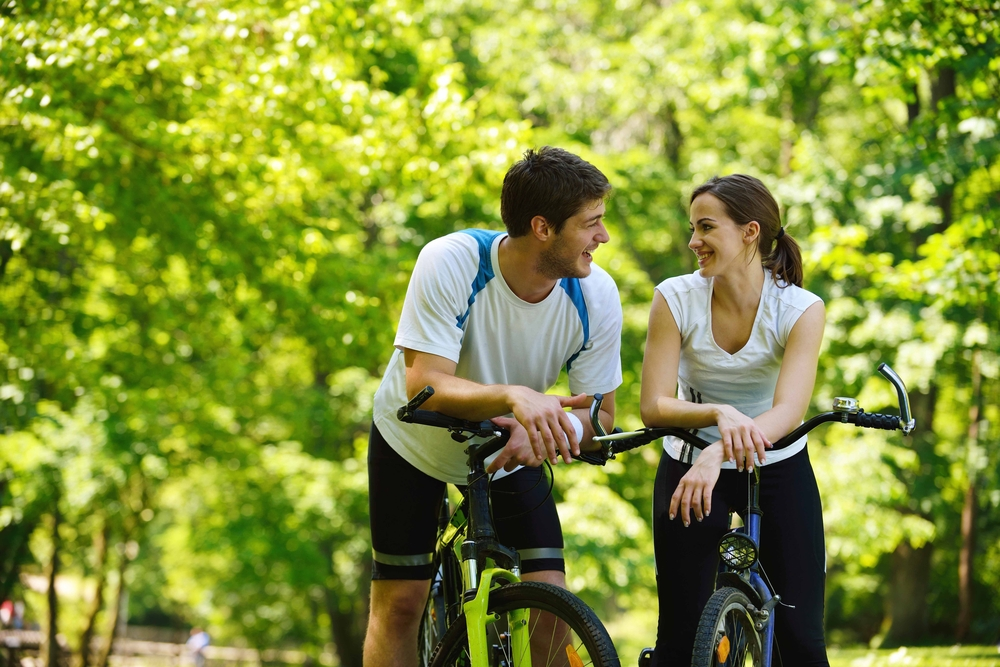 boy and girl sitting on bicycles in front of trees