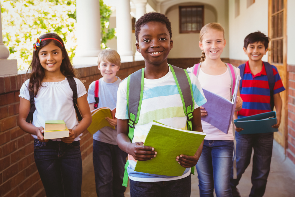 five young students with notebooks and backpacks on first day of school