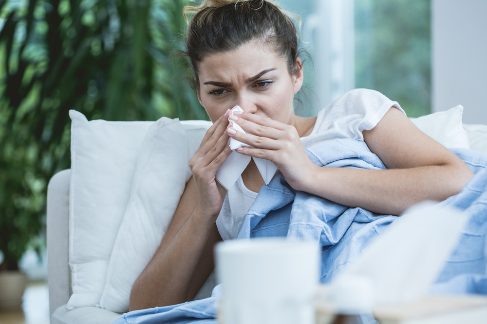 women blowing her nose with tissue