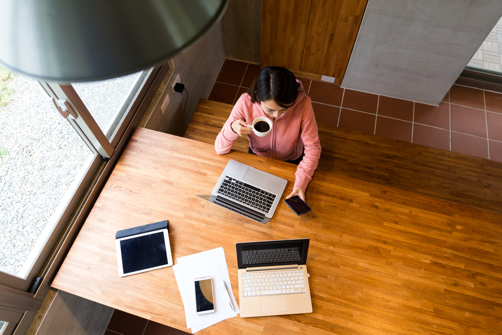 aerial shot of woman drinking coffee in front of laptop on wooden table