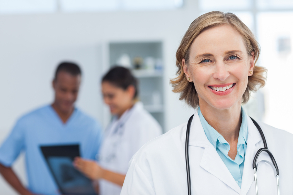 female doctor smiling in front of two blurred colleagues looking at x-ray