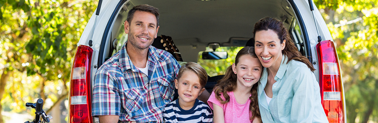 Family of four smiling from the back of their car