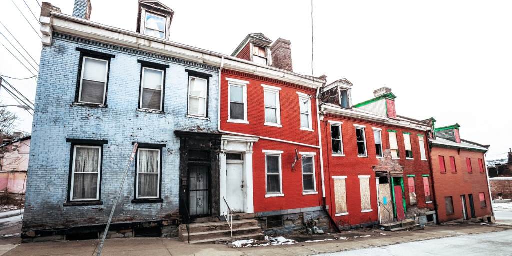 blue and red broken down apartments building side by side