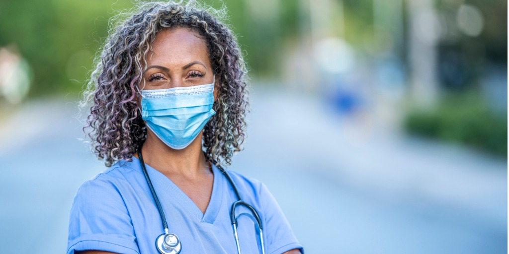 female medical professional wearing mask and blue scrubs