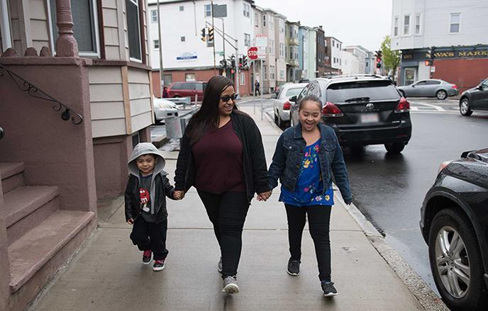 family of three walking down the street