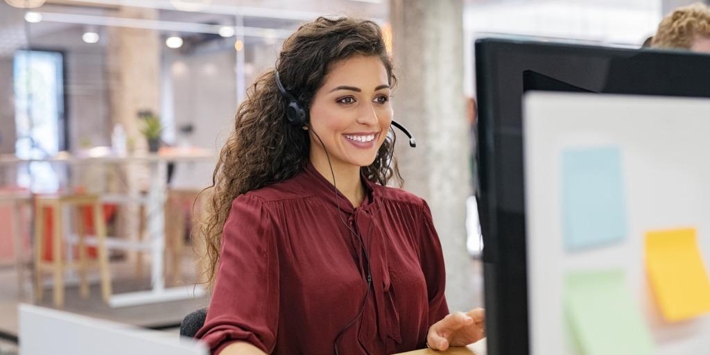 woman wearing headset smiling at computer