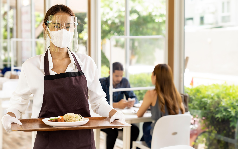 double masked waitress holding food tray