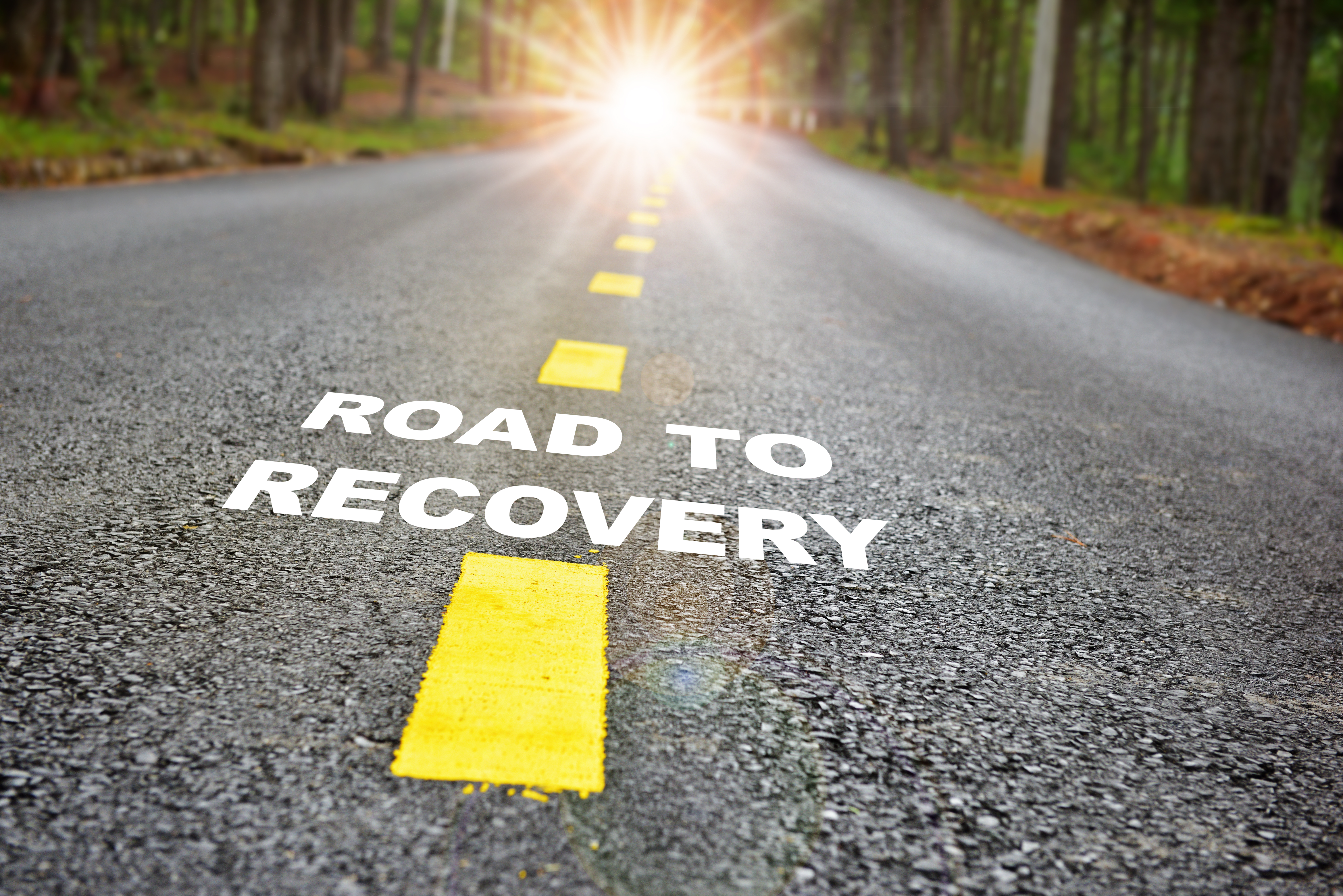 road to recovery on paved road and sunlight towards the end