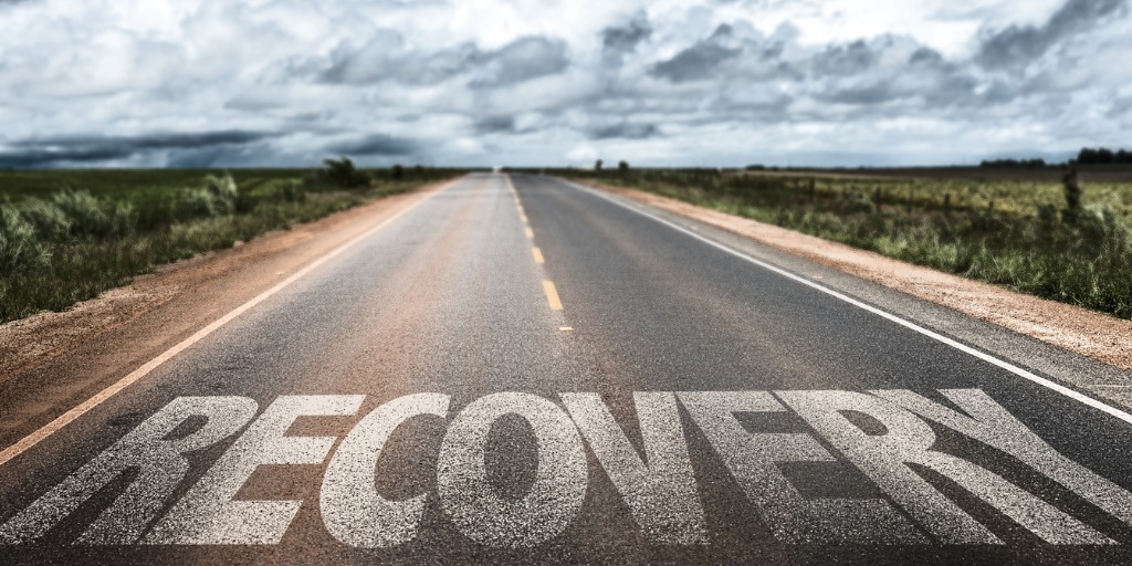 the word recovery on a paved road