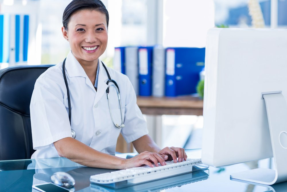 doctor smiling while typing on computer