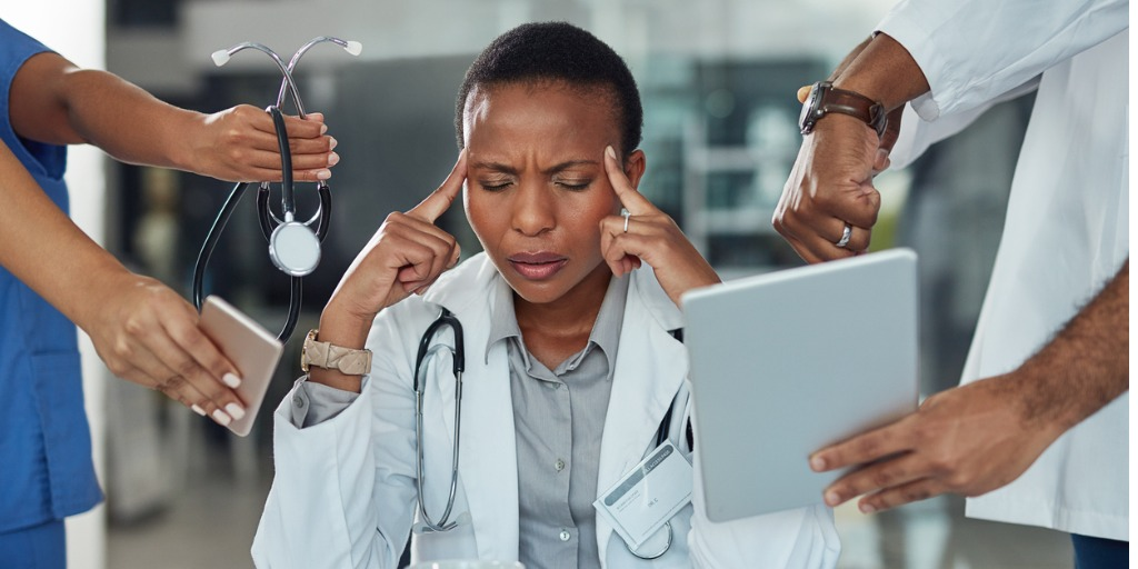 doctor burned out and rubbing her head