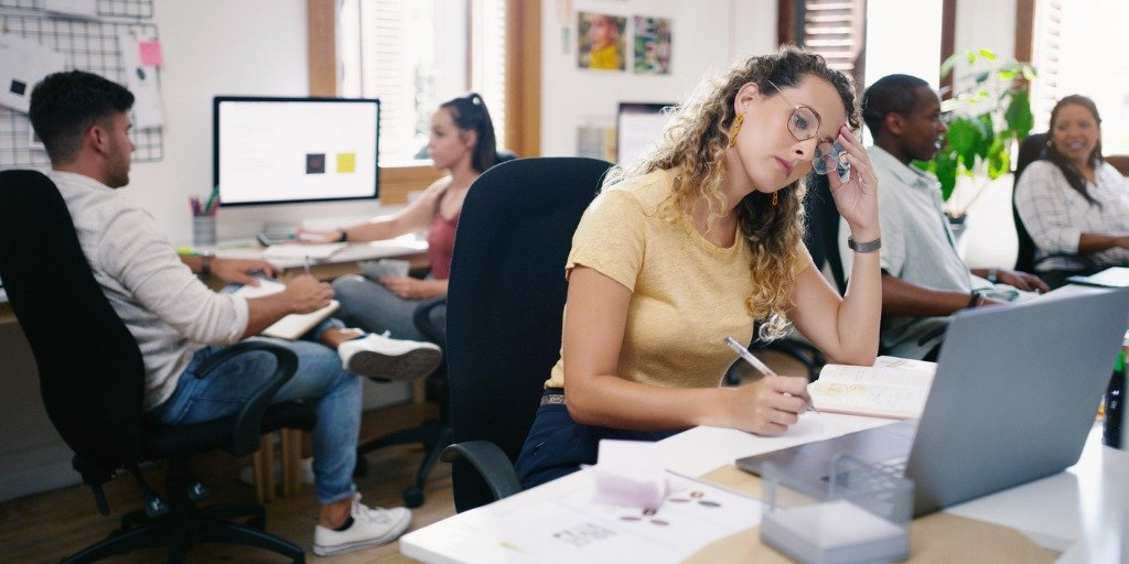 employee sitting at desk discouraged with head in hand