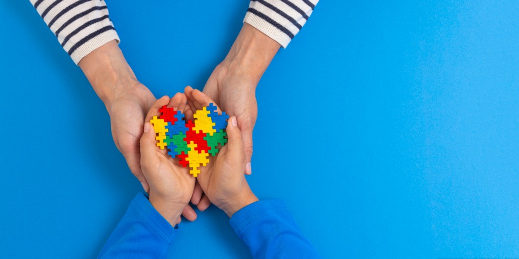 hands holding colored puzzle pieces for Autism awareness