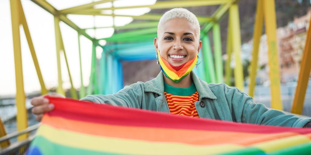 woman holding pride flag on rainbow bridge
